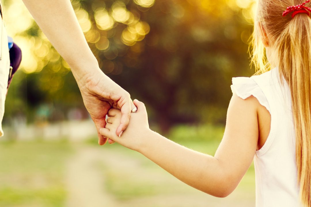 Child holding parents hand on a walk